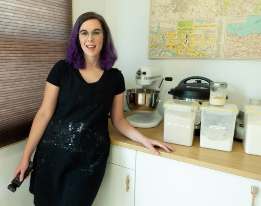 Amber poses wearing an apron next to a kitchen counter with baking supplies on it