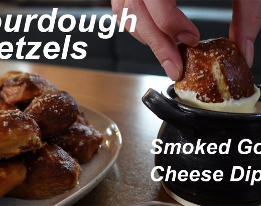 A plate of pretzels next to a single pretzel nugget being dipped into cheese.